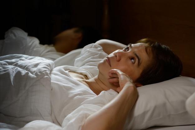 Donna con insonnia sdraiata a letto con gli occhi aperti