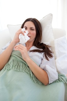 Donna con l'influenza sdraiata sul divano