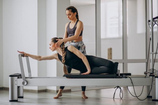 Donna con l'istruttore di pilates che si esercita nei pilates