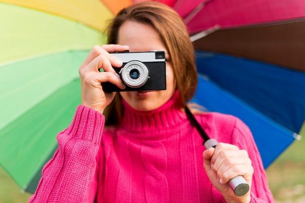 Donna con l'ombrello variopinto che prende una foto con la sua macchina fotografica