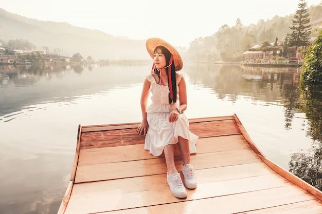 Donna con la barca di stile cinese nel lago con la luce e la nebbia di mattina.