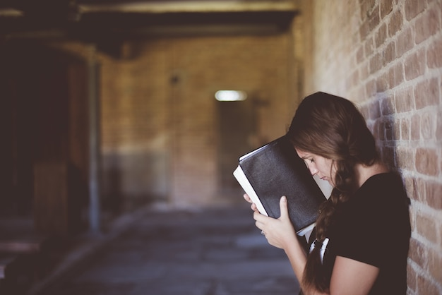 Donna con la bibbia contro la testa mentre prega