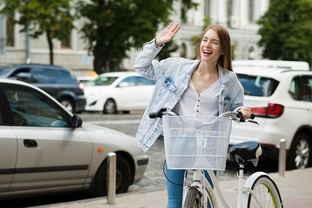 Donna con la bicicletta agitando