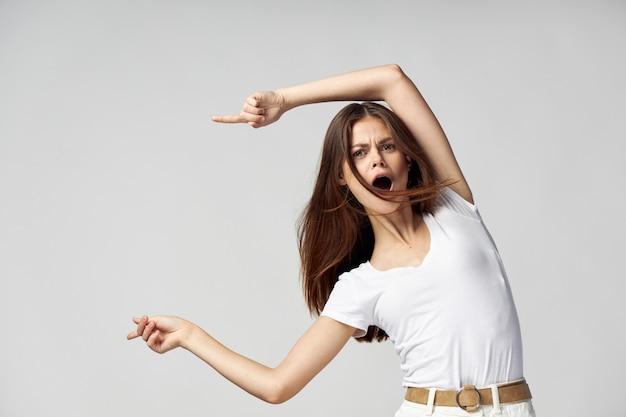 Donna con la bocca aperta mostra le dita alla maglietta bianca di emozioni laterali