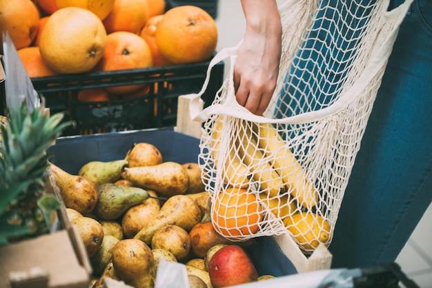 Donna con la borsa della maglia piena di verdure fresche shopping al negozio, zero concetto di rifiuti