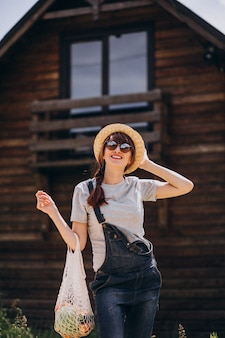 Donna con la borsa di eco con frutta in una campagna