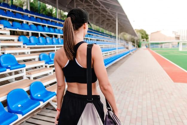 Donna con la borsa sportiva prima dell'allenamento sullo stadio al mattino