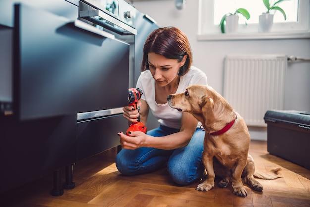 Donna con la cucina della costruzione di cane e usando un trapano senza cordone