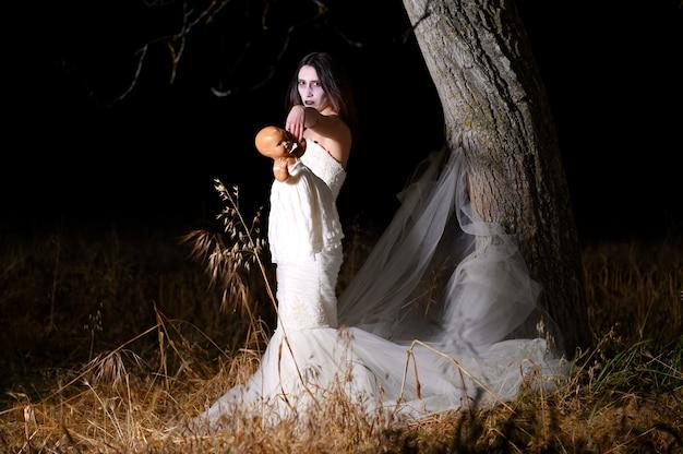 Donna con la faccia bianca e il vestito che tiene una bambola