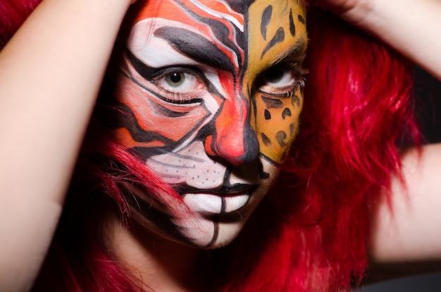 Donna con la faccia di tigre nel concetto di halloween