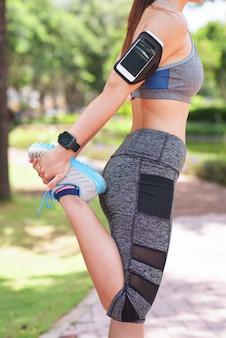 Donna con la fascia da braccio che allunga nel parco