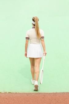 Donna con la foto della racchetta di tennis da dietro
