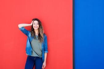 Donna con la mano nei capelli su sfondo blu e rosso