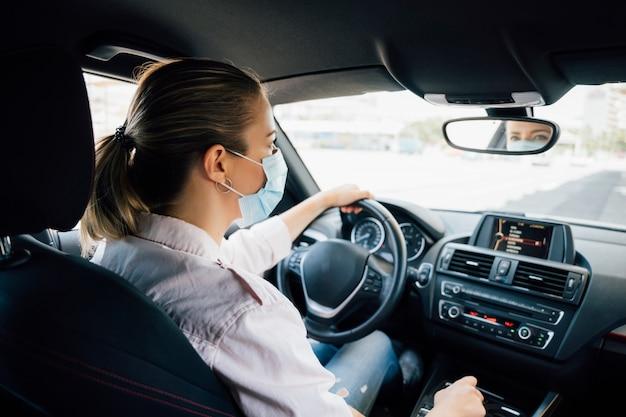 Donna con la maschera che guida la sua auto durante la pandemia di coronavirus