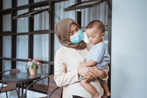 Donna con la maschera che trasporta suo figlio