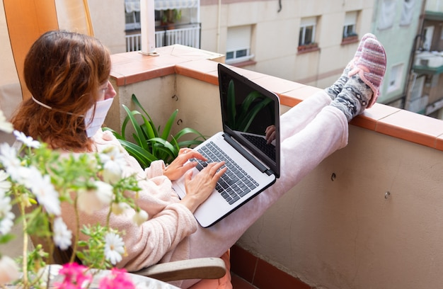 Donna con la maschera confinata a casa con il computer portatile