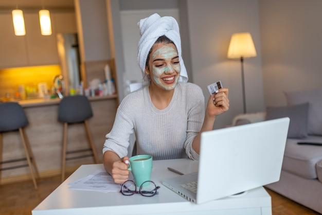 Donna con la maschera facciale che compera online dalla sua casa. tempo libero a casa.