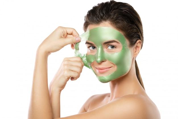 Donna con la maschera verde staccata sul suo viso