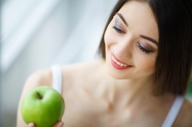 Donna con la mela. bella ragazza con un sorriso bianco, denti sani.