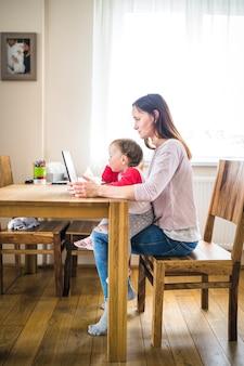 Donna con la neonata in grembo usando il portatile