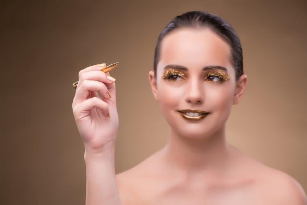 Donna con la penna d'oro nel concetto di moda