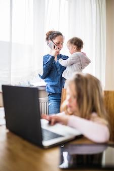 Donna con la sua bambina parlando sul cellulare