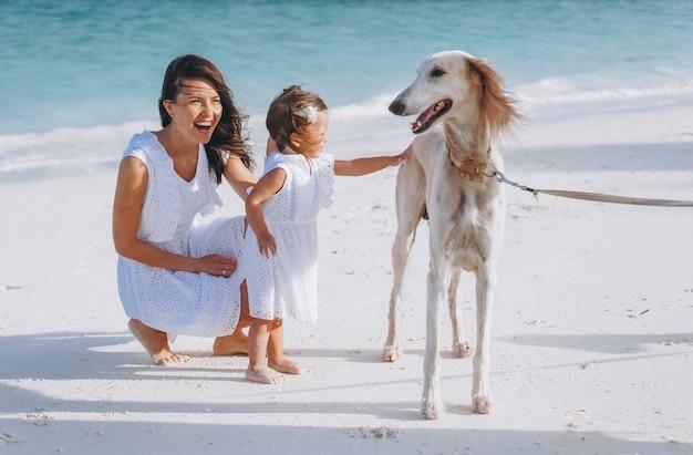 Donna con la sua piccola figlia che gioca con i cani sulla spiaggia dall'oceano