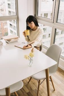 Donna con la tazza che legge al tavolo