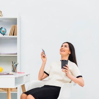 Donna con la tazza di caffè e smartphone ridendo in ufficio