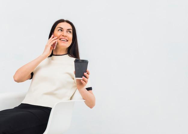 Donna con la tazza di caffè parlando per telefono