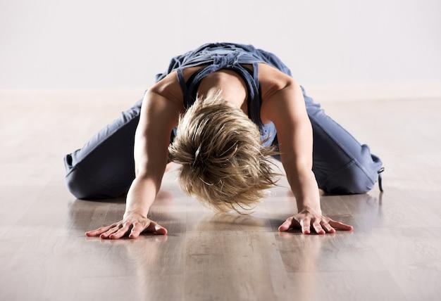 Donna con la testa in giù mentre allunga i muscoli dell'anca