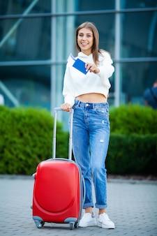 Donna con la valigia rossa vicino all'aeroporto