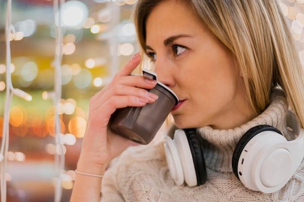 Donna con le cuffie al collo che beve dalla tazza