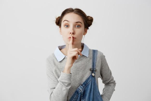Donna con le espressioni facciali educate che tengono il dito indice sulle labbra. casalinga femminile che chiede di mantenere il silenzio per non disturbare i suoi figli durante il sonno.