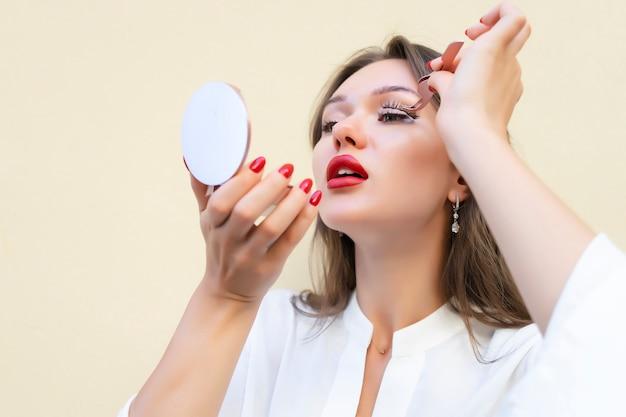 Donna con le labbra rosse grassottelle che tengono le ciglia finte magnetiche su fondo beige