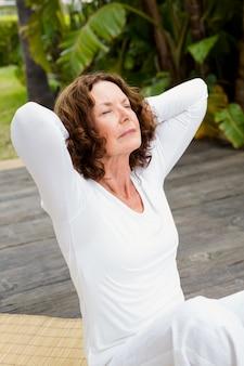 Donna con le mani dietro la testa mentre si fa yoga