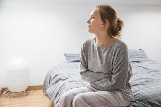Donna con le mani sullo stomaco soffre di dolore, guardando da parte