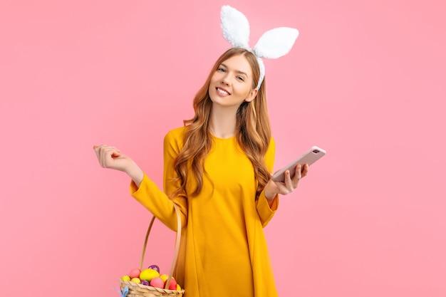 Donna con le orecchie del coniglietto che tiene un telefono