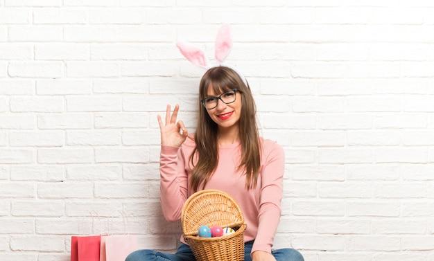 Donna con le orecchie del coniglietto per le vacanze di pasqua che si siedono sul pavimento che mostra un segno giusto con le dita