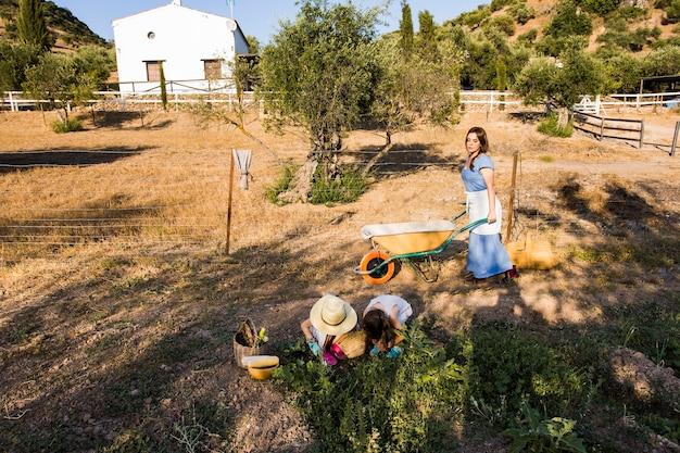 Donna con le sue due figlie che lavorano nel campo