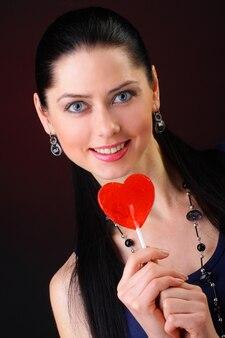 Donna con lecca-lecca a forma di cuore rossa
