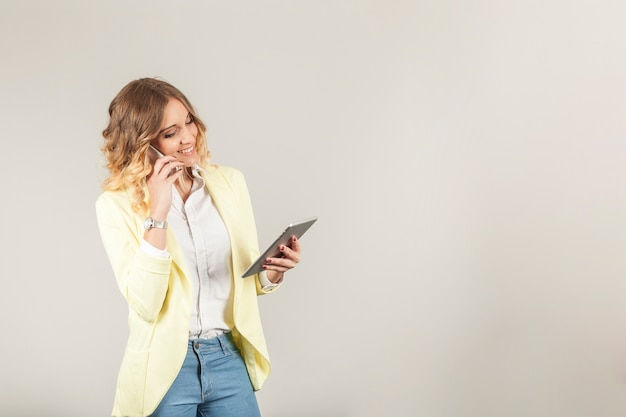 Donna con lo smartphone su orecchio e tablet