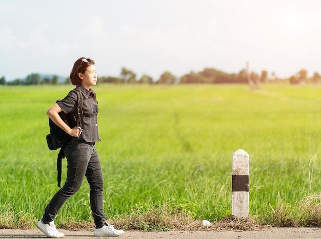 Donna con lo zaino autostop lungo una strada
