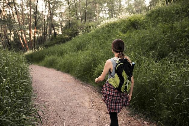 Donna con lo zaino che cammina nel sentiero forestale