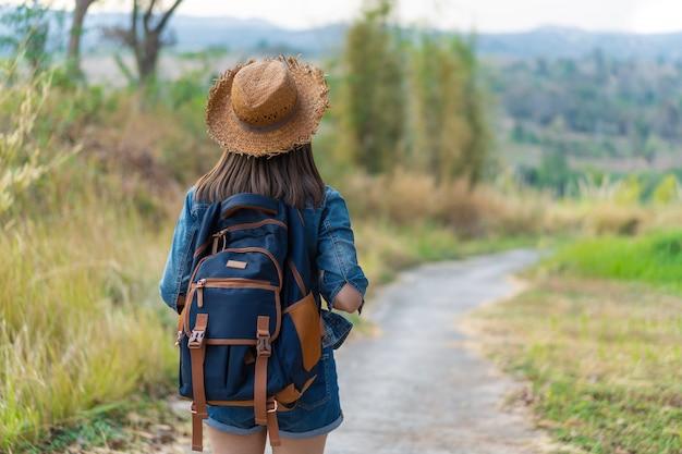 Donna con lo zaino che cammina sul sentiero per pedoni in natura