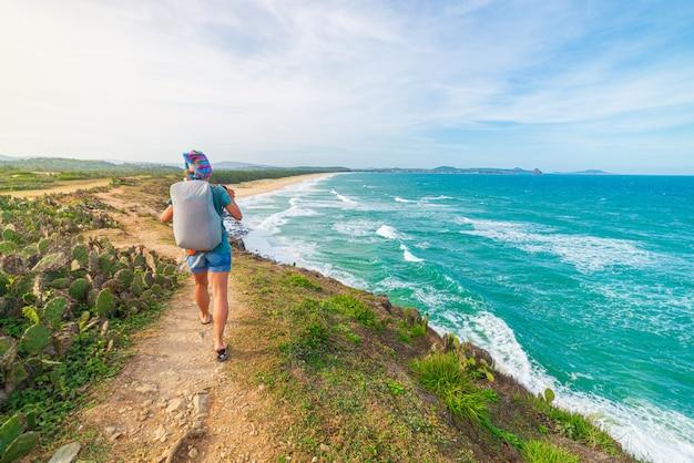 Donna con lo zaino che esamina costa tropicale dalla scogliera qui sopra. destinazione di viaggio in vietnam, provincia di phu yen tra da nang e nha trang. mare d'ondeggiamento blu splendido della spiaggia di sabbia