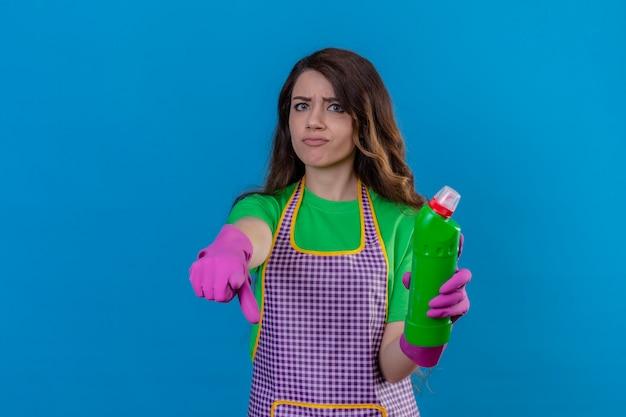 Donna con lunghi capelli ondulati che indossa grembiule e guanti di gomma che tiene con una bottiglia di materiale per la pulizia che punta dispiaciuto e frustrato arrabbiato e furioso con te sul blu