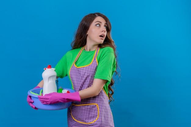Donna con lunghi capelli ondulati che indossa un grembiule e guanti di gomma tenendo il bacino pieno di strumenti per la pulizia guardando da parte con sorpresa faccia paura ed è uscito in piedi sul blu
