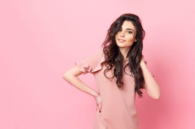 Donna con lunghi capelli ricci in un abito rosa.