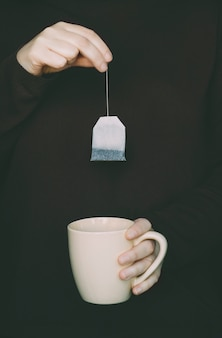 Donna con maglione marrone in possesso di una bustina di tè per lasciarlo in una tazza beige